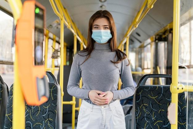 Mulher jovem viajando de ônibus municipal com máscara cirúrgica