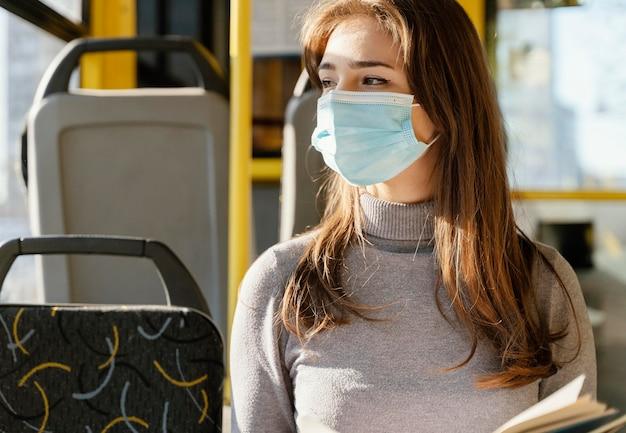 Mulher jovem viajando de ônibus municipal lendo um livro
