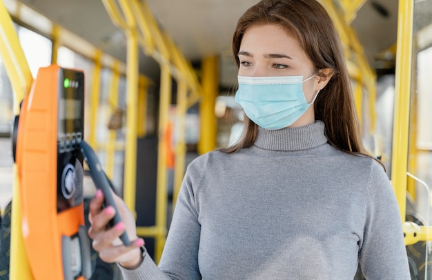 Mulher jovem viajando de ônibus municipal, pagando com cartão de ônibus