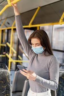 Mulher jovem viajando de ônibus urbano usando smartphone