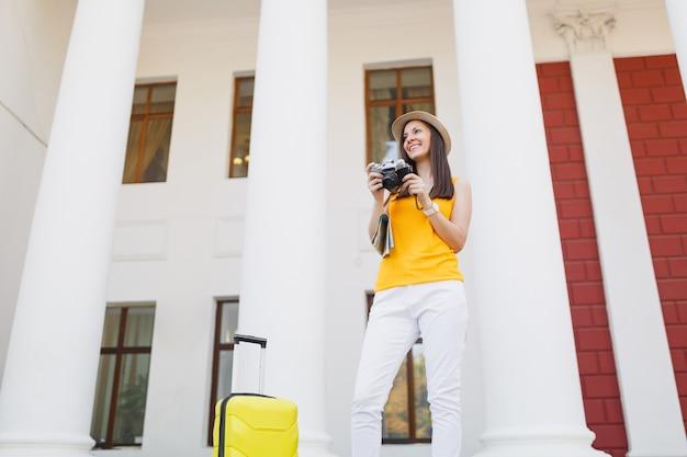 Mulher jovem viajante alegre turista em roupas casuais com mapa da cidade mala segurando a câmera fotográfica vintage retrô na cidade ao ar livre. garota viajando para o exterior na fuga de fins de semana. estilo de vida da viagem de turismo.