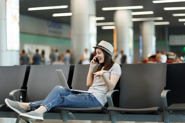 Mulher jovem viajante alegre, turista, trabalhando em um laptop, fala no celular, liga para um amigo, reserva um táxi, espera em um hotel no saguão do aeroporto