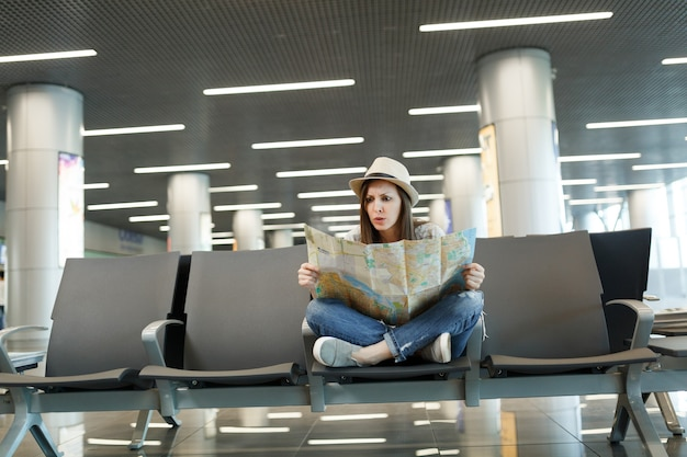 Mulher jovem viajante assustada com as pernas cruzadas, segurando um mapa de papel, procurando uma rota esperando no saguão do aeroporto internacional