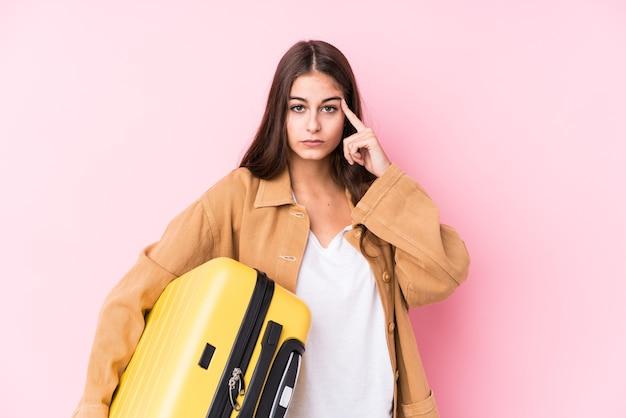 Mulher jovem viajante caucasiana segurando um templo isolado de ponta de mala com o dedo, pensando, focado em uma tarefa.