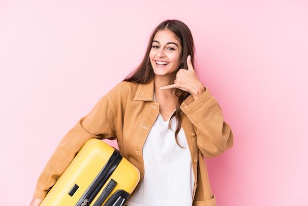 Mulher jovem viajante caucasiano segurando uma mala isolatedshowing um gesto de chamada de telefone móvel com os dedos.