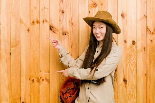 Mulher jovem viajante chinês animado apontando com os dedos indicadores de distância.