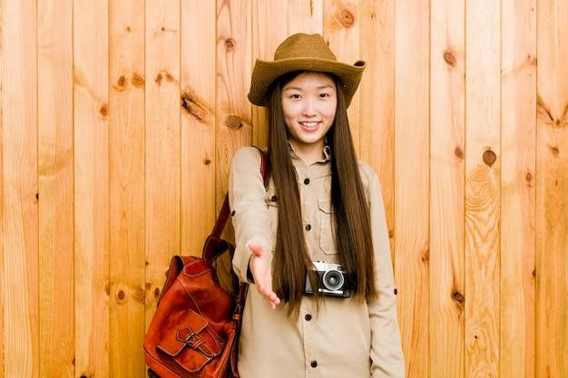 Mulher jovem viajante chinês, esticando a mão na câmera em gesto de saudação.