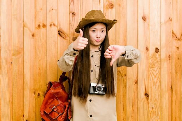Mulher jovem viajante chinês mostrando os polegares para cima e os polegares para baixo, difícil escolher o conceito