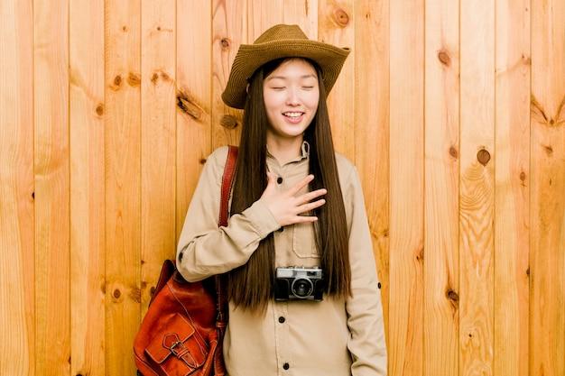 Mulher jovem viajante chinês ri alto, mantendo a mão no peito.