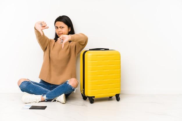 Mulher jovem viajante chinês sentado no chão com uma mala mostrando o polegar para baixo e expressando antipatia.