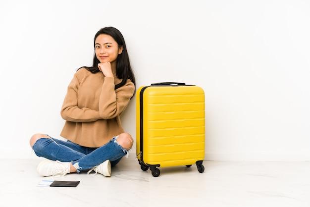 Mulher jovem viajante chinês sentado no chão com uma mala sorrindo feliz e confiante, tocando o queixo com a mão.