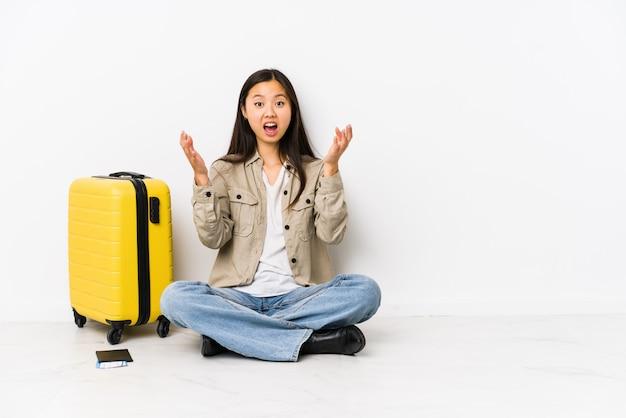 Mulher jovem viajante chinês sentado segurando um cartão de embarque, recebendo uma surpresa agradável, animado e levantando as mãos.