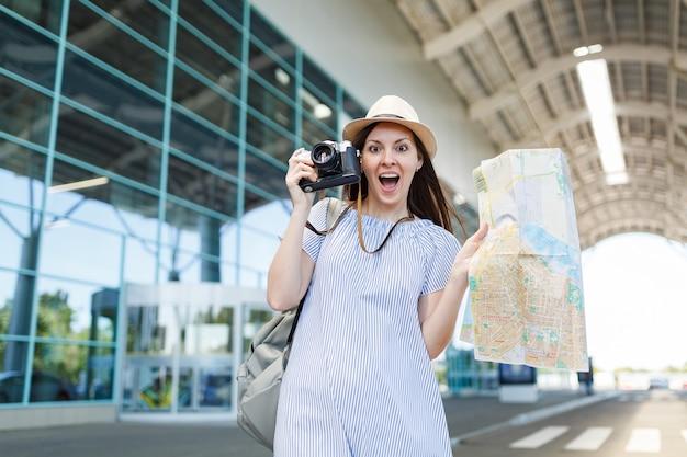 Mulher jovem viajante chocada com um chapéu segurando uma câmera fotográfica vintage retrô, mapa de papel no aeroporto internacional