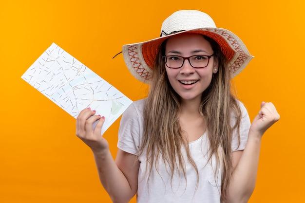 Mulher jovem viajante com camiseta branca e chapéu de verão, segurando o mapa punho cerrado, animada e feliz, sorrindo em pé sobre a parede laranja