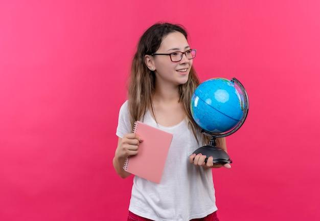 Mulher jovem viajante com camiseta branca segurando um globo e um caderno olhando de lado sorrindo positiva e feliz em pé sobre a parede rosa