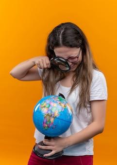 Mulher jovem viajante com camiseta branca segurando um globo olhando para ele através da lupa em pé sobre a parede laranja