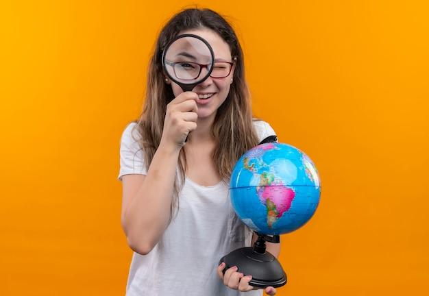 Mulher jovem viajante com camiseta branca segurando um globo, olhando pela lupa, parecendo surpresa e feliz em pé sobre a parede laranja