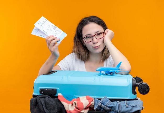 Mulher jovem viajante com camiseta branca segurando uma mala cheia de roupas e passagens aéreas inclinando a cabeça na mão olhando sorrindo em pé