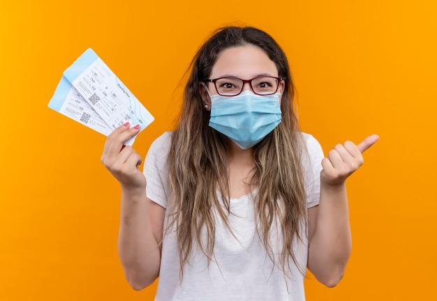 Mulher jovem viajante com camiseta branca usando máscara protetora facial segurando passagens aéreas sorrindo e mostrando os polegares em pé sobre a parede laranja