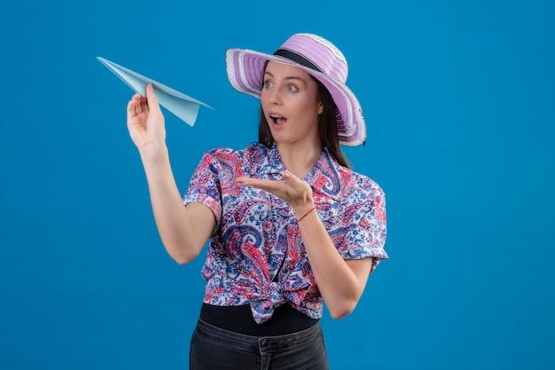 Mulher jovem viajante com chapéu de verão segurando um avião de papel apontando com o braço para ele, parecendo surpresa em pé sobre um fundo azul