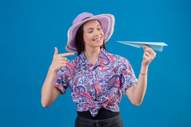 Mulher jovem viajante com chapéu de verão segurando um avião de papel apontando com o dedo para ele e sorrindo com uma cara feliz em pé sobre um fundo azul