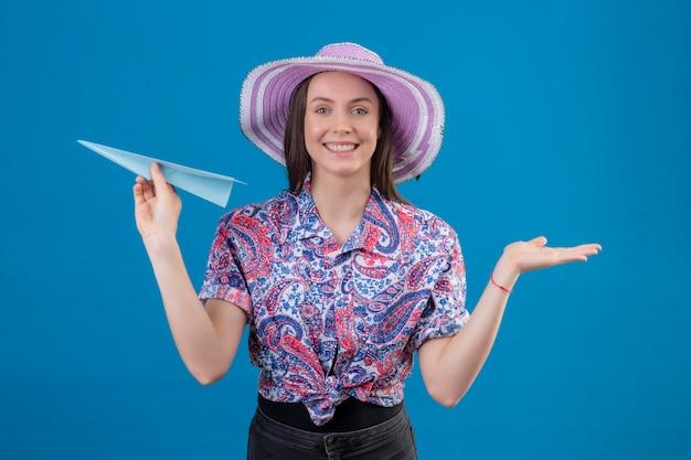 Mulher jovem viajante com chapéu de verão segurando um avião de papel, apresentando-se com o braço da mão, olhando para a câmera, sorrindo alegremente com uma cara feliz em pé sobre um fundo azul