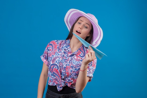 Mulher jovem viajante com chapéu de verão segurando um avião de papel brincalhão e feliz em pé sobre um fundo azul