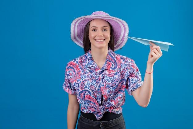 Mulher jovem viajante com chapéu de verão segurando um avião de papel, olhando para a câmera, positiva e feliz, sorrindo alegremente em pé sobre um fundo azul
