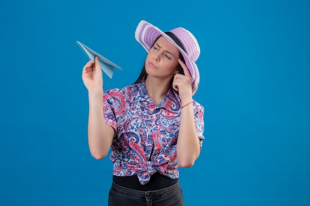 Mulher jovem viajante com chapéu de verão segurando um avião de papel olhando para ele com uma expressão pensativa, tendo dúvidas pensando em pé sobre um fundo azul