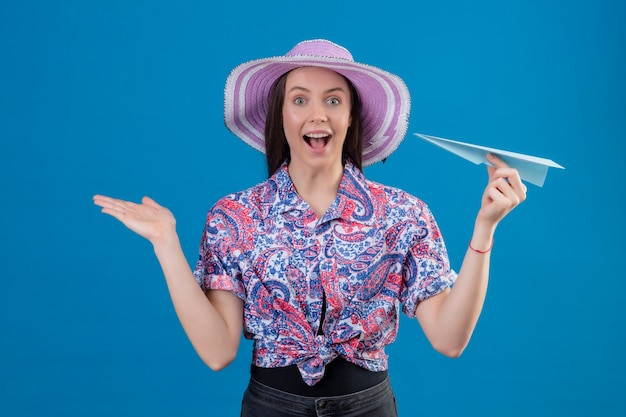 Mulher jovem viajante com chapéu de verão segurando um avião de papel, parecendo surpresa e feliz em pé com a mão levantada sobre fundo azul