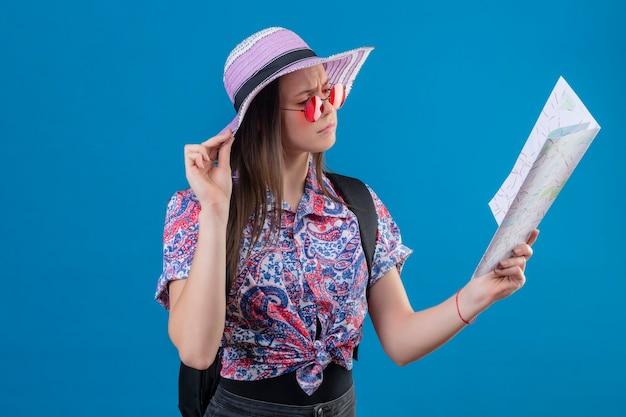 Mulher jovem viajante com chapéu de verão usando óculos de sol vermelhos segurando um mapa e olhando para ele com uma cara carrancuda em pé sobre um fundo azul