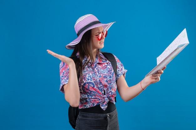 Mulher jovem viajante com chapéu de verão usando óculos de sol vermelhos segurando um mapa, olhando para ele, confuso com o braço aberto, nenhuma ideia do conceito de pé sobre o fundo azul
