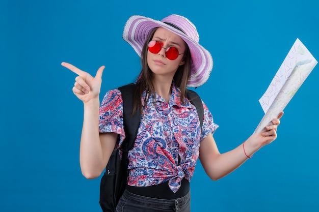 Mulher jovem viajante com chapéu de verão usando óculos escuros vermelhos segurando mapa olhando para o lado com uma expressão pensativa apontando com o dedo para o lado pensando tendo dúvidas em pé sobre um fundo azul