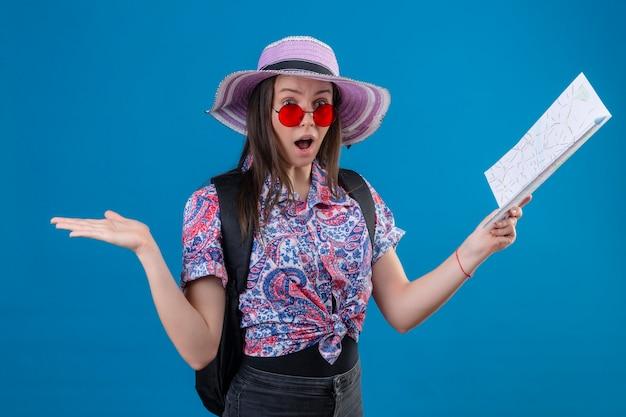 Mulher jovem viajante com chapéu de verão usando óculos escuros vermelhos segurando um mapa, olhando para a câmera espantada e surpresa com a boca aberta sobre um fundo azul