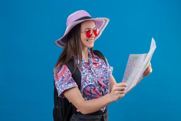 Mulher jovem viajante com chapéu de verão usando óculos escuros vermelhos segurando um mapa, olhando para ele, sorrindo com uma cara feliz em pé sobre um fundo azul
