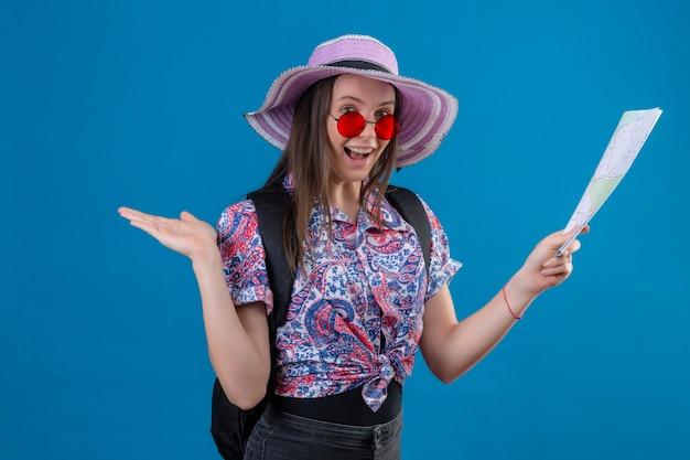 Mulher jovem viajante com chapéu de verão usando óculos escuros vermelhos segurando um mapa, parecendo positiva e feliz em pé com o braço levantado sobre fundo azul