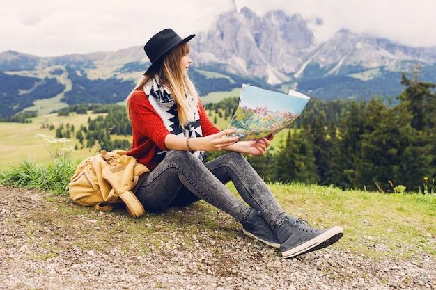 Mulher jovem viajante com mochila e chapéu sentada na grama e procurando a direção certa no mapa