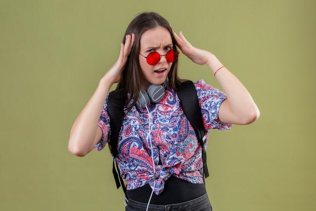Mulher jovem viajante com mochila e fones de ouvido, usando óculos escuros vermelhos, tocando a cabeça, olhando irritado com dor de cabeça em cima de parede verde