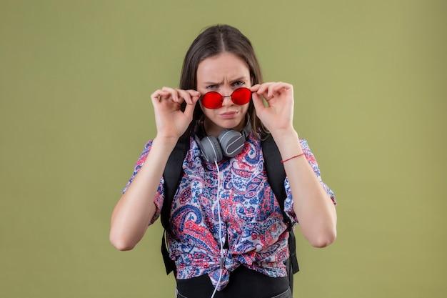 Mulher jovem viajante com mochila e fones de ouvido, usando óculos escuros vermelhos, tocando-os olhando para a câmera com expressão suspeita em pé sobre a parede verde