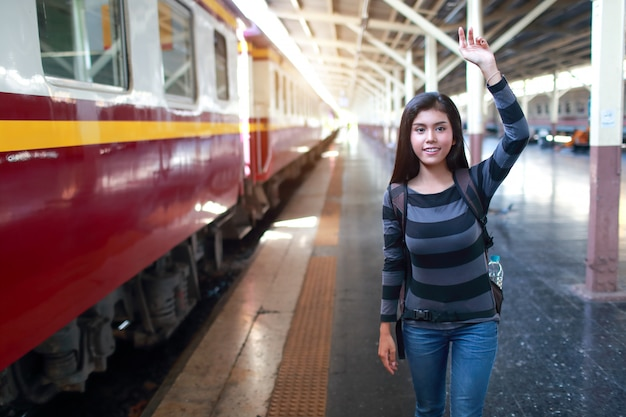 Mulher jovem viajante com mochila esperando trem