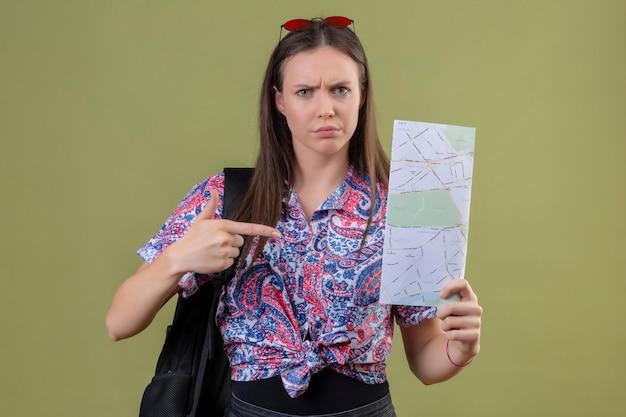 Mulher jovem viajante com óculos de sol vermelhos na cabeça e com uma mochila segurando um mapa apontando com o dedo indicador para ele com uma cara carrancuda em pé sobre um fundo verde