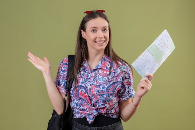 Mulher jovem viajante com óculos de sol vermelhos na cabeça e mochila segurando o mapa, sorrindo alegremente, apresentando-se com o braço da mão em pé sobre o fundo verde