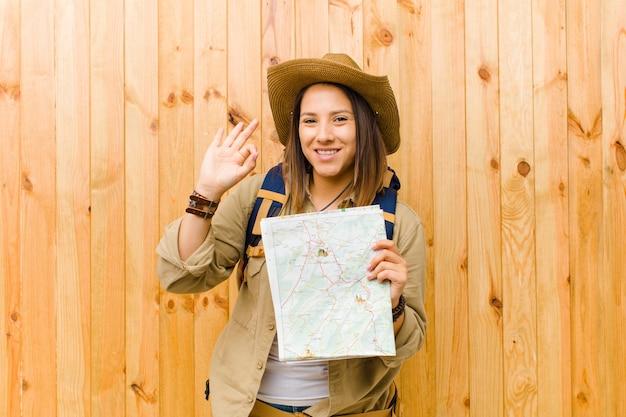 Mulher jovem viajante com um mapa contra a parede de madeira