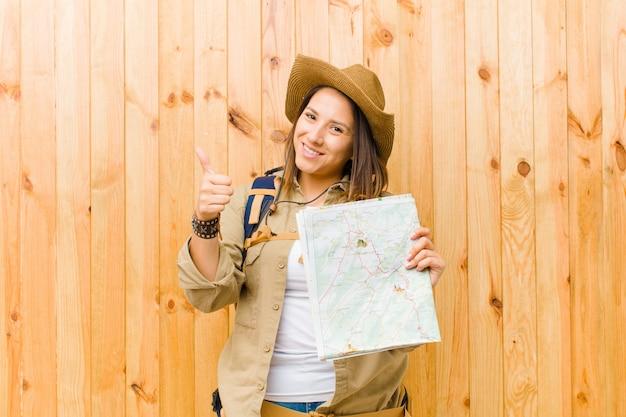 Mulher jovem viajante com um mapa na parede de madeira
