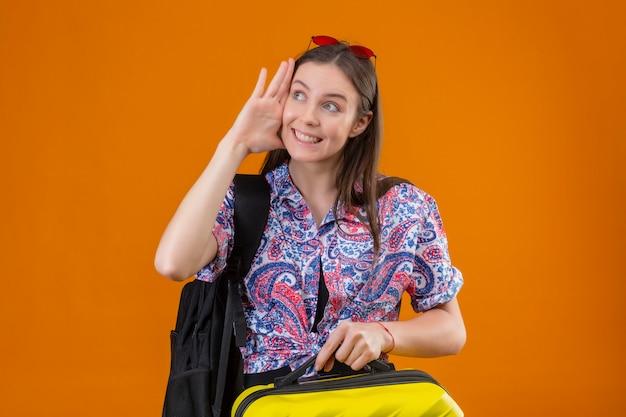 Mulher jovem viajante de óculos vermelhos na cabeça com mochila segurando a mala, olhando de lado, sorrindo alegremente, segurando a mão perto da orelha, tentando ouvir a conversa de som