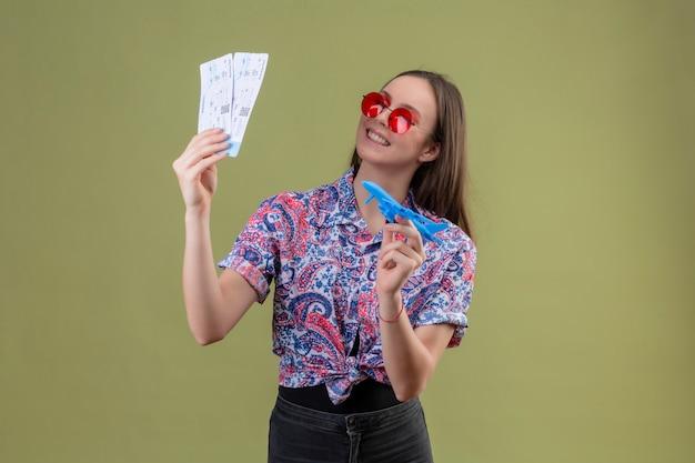 Mulher jovem viajante de óculos vermelhos segurando bilhetes e avião de brinquedo, olhando de lado com cara feliz sorrindo alegremente sobre parede verde