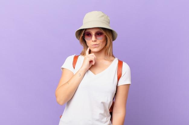 Mulher jovem viajante e turista se sentindo perplexa e confusa coçando a cabeça
