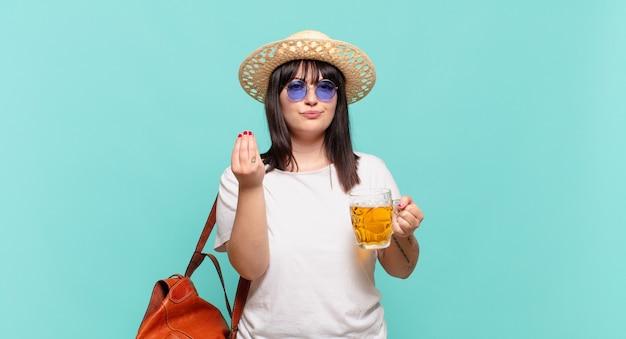 Mulher jovem viajante fazendo capice ou gesto de dinheiro, mandando você pagar suas dívidas!