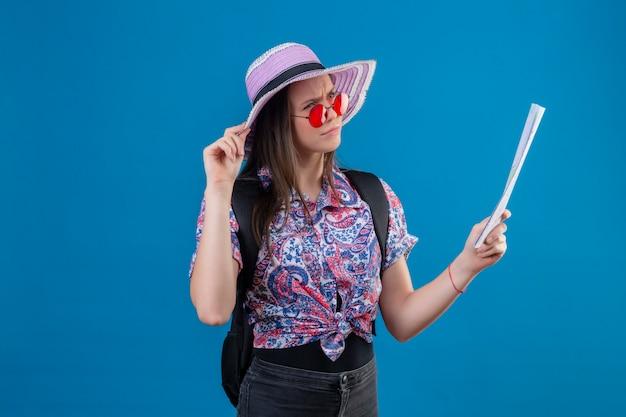 Mulher jovem viajante no chapéu do verão de óculos vermelhos, segurando o mapa, olhando de lado com o pensamento de expressão pensativa, tendo dúvidas sobre a parede azul
