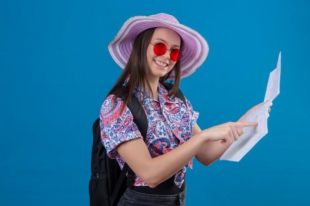 Mulher jovem viajante no chapéu do verão usando óculos de sol vermelhos, segurando o mapa apontando com o dedo para ele sorrindo alegremente sobre parede azul